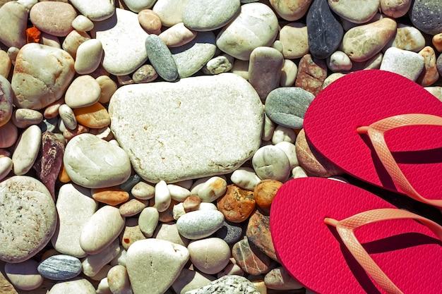 Chinelos cor-de-rosa na praia de seixos. conceito de férias de verão do mar. vista do topo. Foto Premium