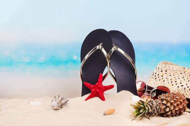 Chinelos de praia, chapéu e óculos de sol na bela praia de areia perto do oceano. espaço da cópia Foto Premium