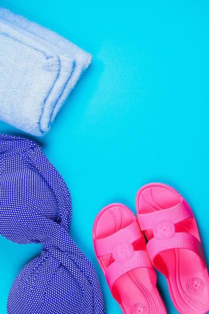 Chinelos, maiô, toalha sobre fundo azul pastel. descanse, viaje. vista do topo. copie o espaço. postura plana. Foto Premium