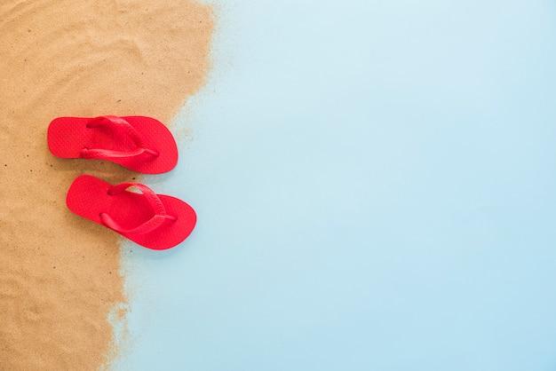 Chinelos vermelhos na areia Foto gratuita