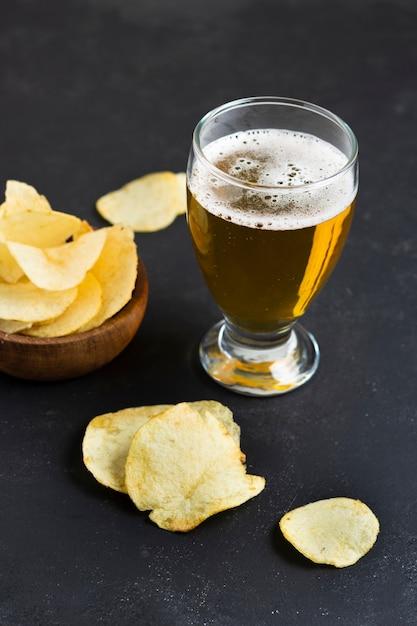 Chips de alto ângulo ao lado de vidro com cerveja Foto gratuita