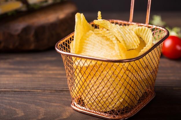 Chips de batata crocante na cesta de cobre Foto Premium