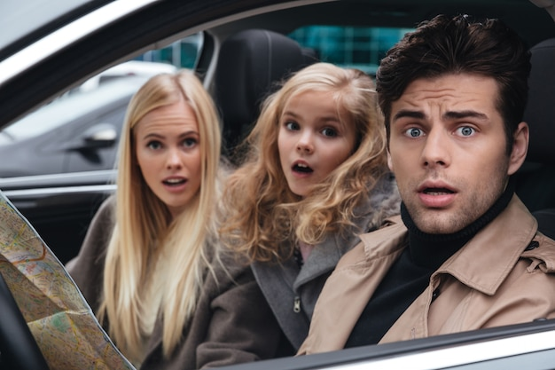 Chocado com medo jovem família segurando o mapa. Foto gratuita