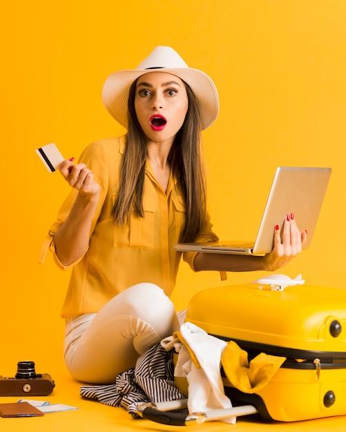 Chocado mulher segurando laptop e cartão de crédito com bagagem ao lado dela Foto gratuita