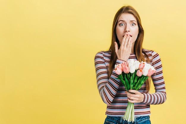 Chocado mulher segurando um buquê de tulipas Foto gratuita