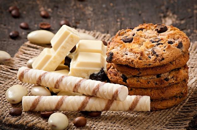 Chocolate branco, amêndoas e biscoitos numa superfície de madeira Foto Premium