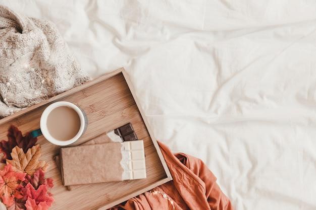 Chocolate e folhas perto de café na cama Foto gratuita