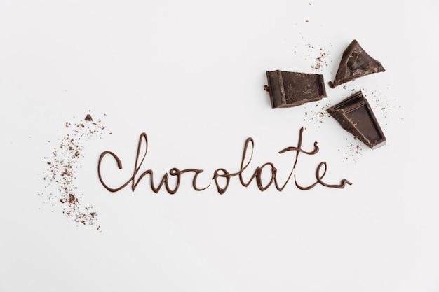 Chocolate palavra perto de pedaços de chocolate e migalhas Foto gratuita