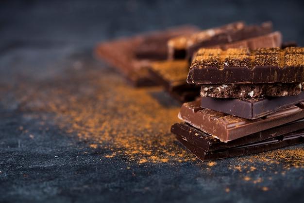 Chocolate quebrado empilhado no fundo preto. Foto Premium