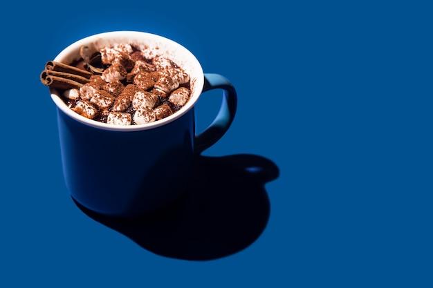 Chocolate quente de natal em um copo azul sobre um fundo azul. Foto Premium