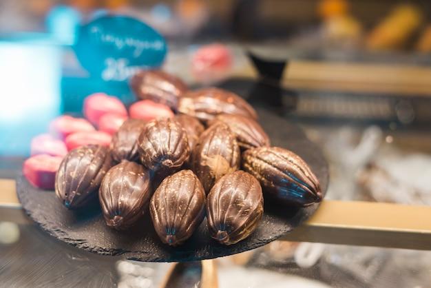 Chocolates de forma de fruta cacau na bandeja de pedra no armário de vidro Foto gratuita