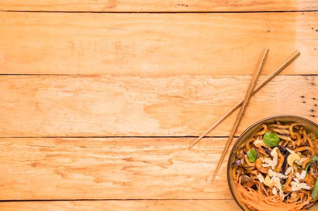 Chopsticks e tigela de macarrão udon enfeitam com camarão; nozes; ervas e camarão sobre a mesa Foto gratuita