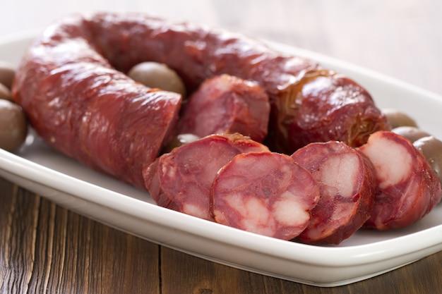 Chourico de linguiça portuguesa defumada em prato branco na mesa de madeira marrom Foto Premium