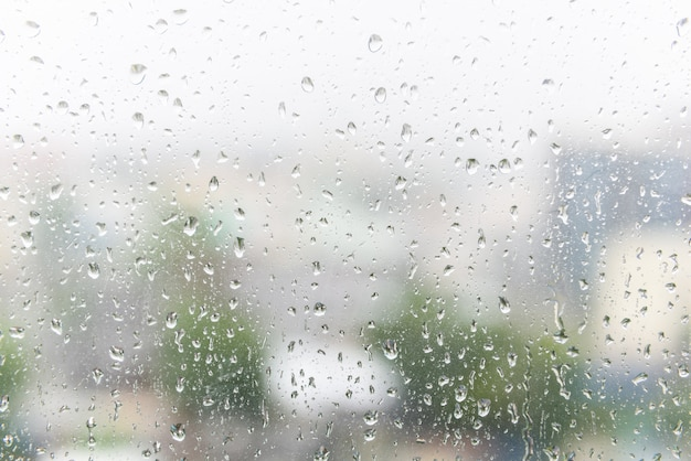 Chova gotas no vidro de janela com fundo borrado escuro. Foto Premium