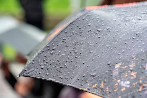 Chovendo, dia, chuva pesada, em, cidade, gotas, ligado, superfície, de, pretas, guarda-chuva, pessoas, com, guarda-chuvas, durante, tempestade Foto Premium
