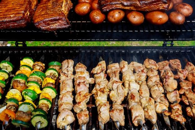 Churrasco com kebab cozinhar grelha de carvão de espetos de carne de frango com cogumelos e pimentos churrasco jantar Foto Premium
