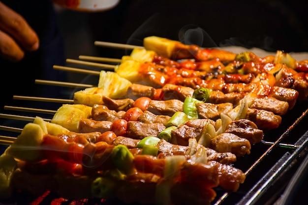 Churrasco de carne grelhada com legumes e molhos de tomate nas grades de aço com o calor. Foto Premium