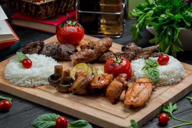 Churrasco de cordeiro e frango com guarnição de arroz em uma placa de bambu Foto gratuita