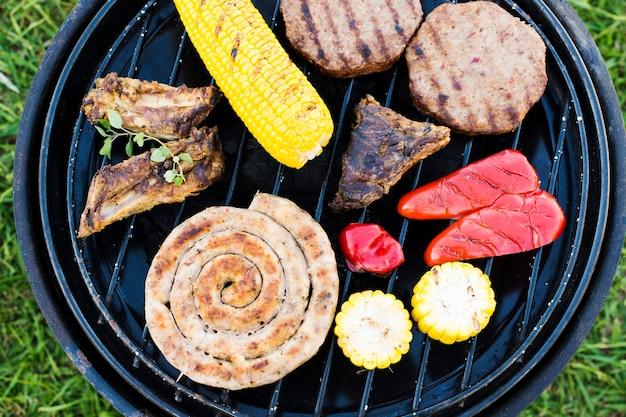Churrasco de salsichas, legumes e carne no grelhador a carvão Foto gratuita