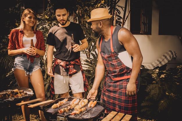 Churrasco e festa. amigos felizes com churrasco na natureza Foto Premium