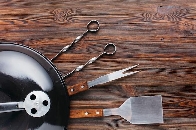 Churrasqueira e utensílio na madeira texturizada Foto gratuita