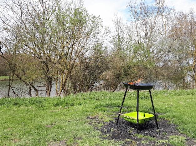 Churrasqueira em pé na grama verde perto do rio Foto Premium