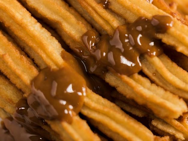 Churros fritos de close-up com chocolate derretido Foto gratuita