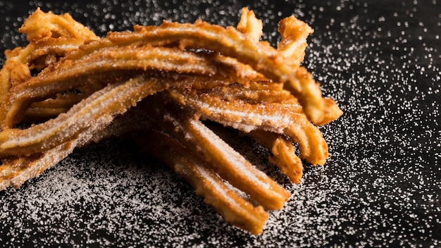 Churros fritos deliciosos com vista alta de açúcar Foto gratuita
