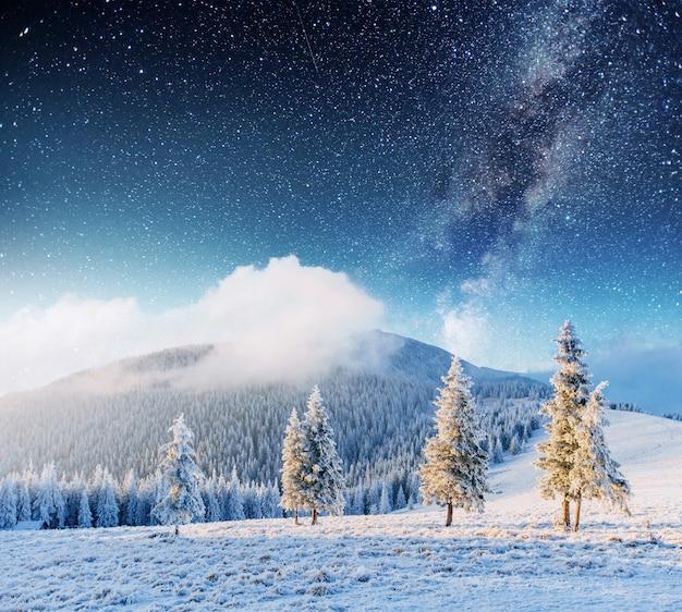 Chuva de meteoros de inverno fantástica e as montanhas cobertas de neve Foto Premium