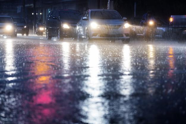 Chuva dura cair à noite com carros embaçados. foco seletivo. Foto Premium