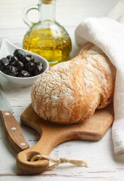 Ciabatta com azeitonas, pão italiano tradicional delicioso fresco, azeitonas e azeite de oliva em uma mesa de madeira branca Foto Premium