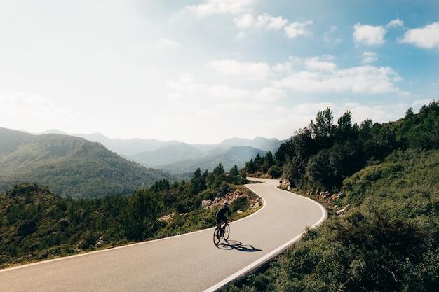 Ciclista andando de bicicleta ao pôr do sol em um roadoor de montanha Foto gratuita