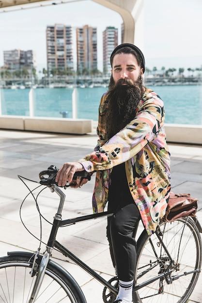Ciclista ativo andando de bicicleta perto do mar Foto gratuita