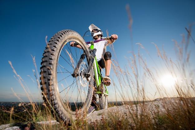 Ciclista com bicicleta de montanha na colina sob o céu azul Foto Premium
