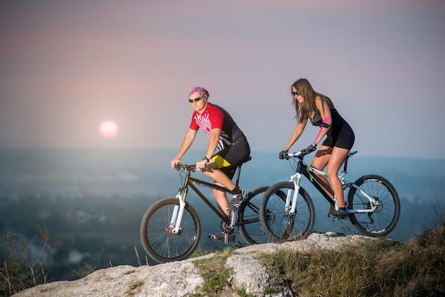 Ciclista, com, namorada, montando, ligado, esportes, bicicletas, em, pôr do sol Foto Premium