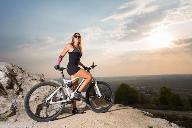 Ciclista de mulher desportivo em uma bicicleta de montanha no penhasco, olhando para a câmera Foto Premium