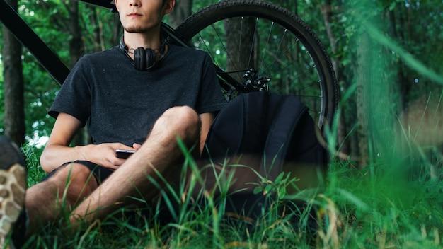 Ciclista descansando sentado no parque junto à árvore. passeio de bicicleta de montanha. ciclista ouvindo música Foto Premium