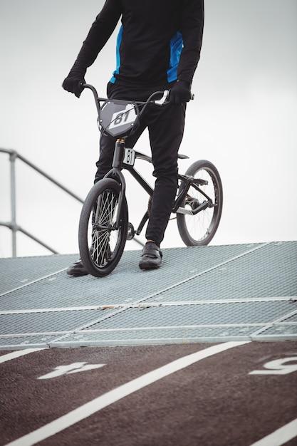 Ciclista em pé com bicicleta bmx na rampa de partida Foto gratuita