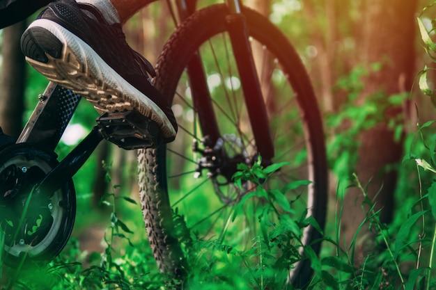 Ciclista em uma bicicleta de montanha na floresta. close-up do pé em pedais de bicicleta. esporte radical Foto Premium