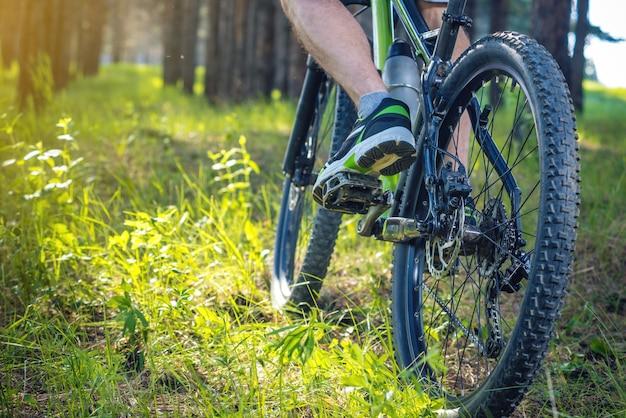 Ciclista em uma bicicleta de montanha verde nas madeiras que montam na grama. o conceito de estilo de vida ativo e extremo Foto Premium