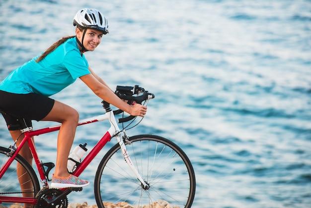 Ciclista feminina andando de bicicleta com o mar Foto Premium