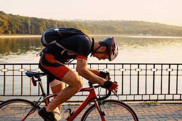 Ciclista jovem e enérgico no parque Foto gratuita