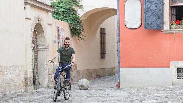 Ciclista masculina andando de bicicleta no pavimento de pedra Foto gratuita