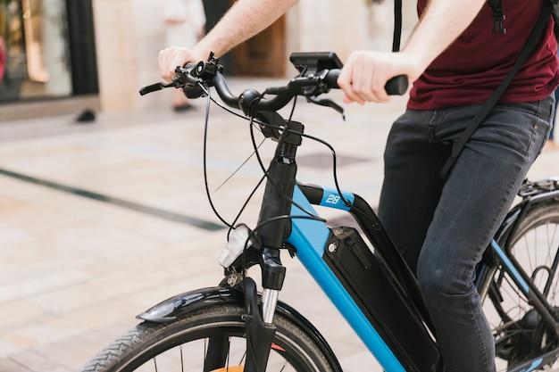 Ciclista, montando, e-bicicleta, através, cidade Foto gratuita