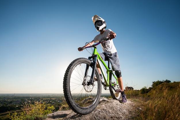 Ciclista no capacete e óculos ficar na bicicleta de montanha Foto Premium