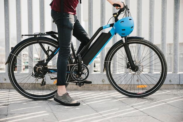 Ciclista urbana, tendo um freio na e-bicicleta Foto gratuita