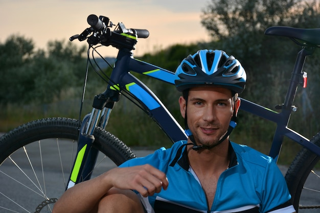 Ciclista vai de bicicleta de montanha ao longo de uma estrada solitária Foto Premium