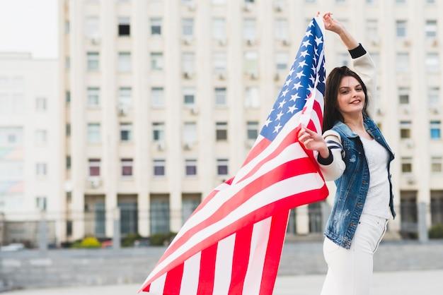 Cidadão americano feminino orgulhoso com bandeira desdobrada Foto gratuita