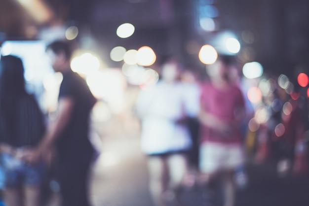 Cidade de noite desfocado lifewith carros, pessoas e lâmpadas de rua, estilo retro Foto Premium
