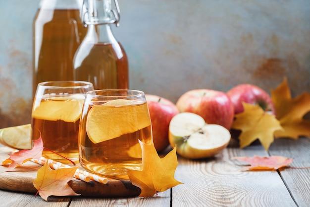 Cidra de maçã orgânica ou suco em uma mesa de madeira Foto Premium
